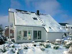 Schnee auf Hausdach und Schneefanggitter