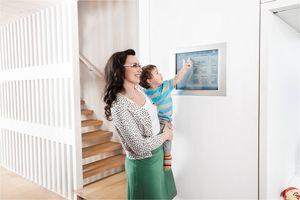 Mutter mit Kind vor Bedienelement von Gebäudeautomation