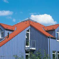 Braas Harzer Pfanne in Klassisch-Rot auf blauem Haus